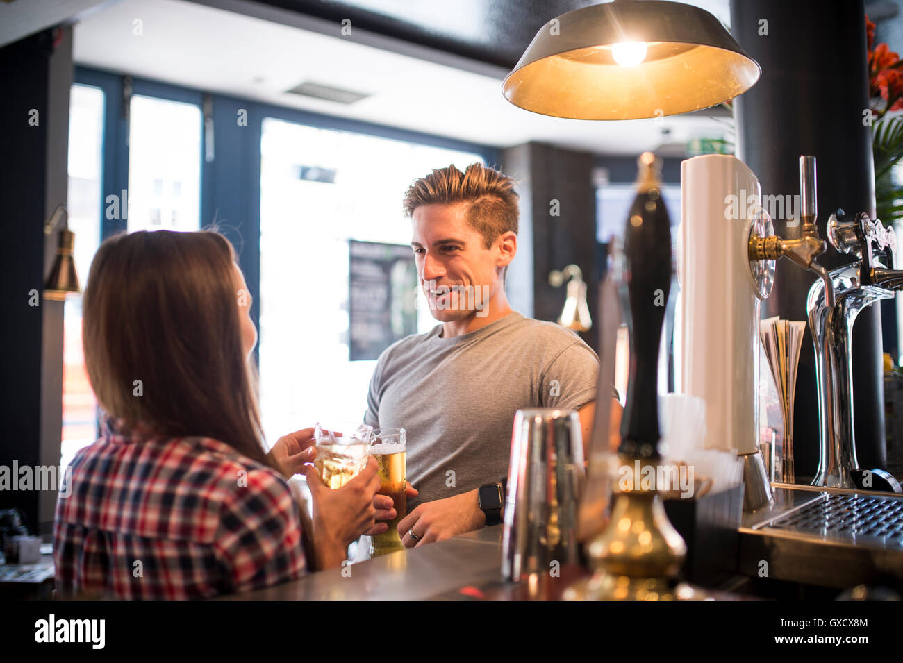 Young couple chatting at city bar - Stock Image