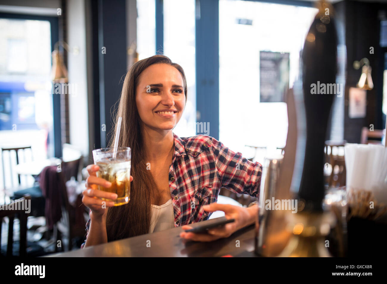 Young woman with smartphone at city bar - Stock Image