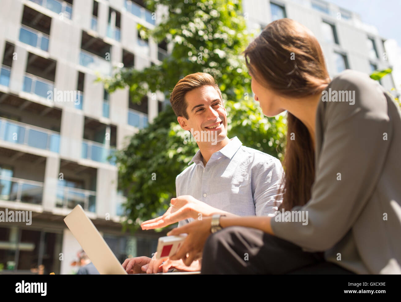 Young businesswoman and man using laptop and chatting, London, UK Stock Photo