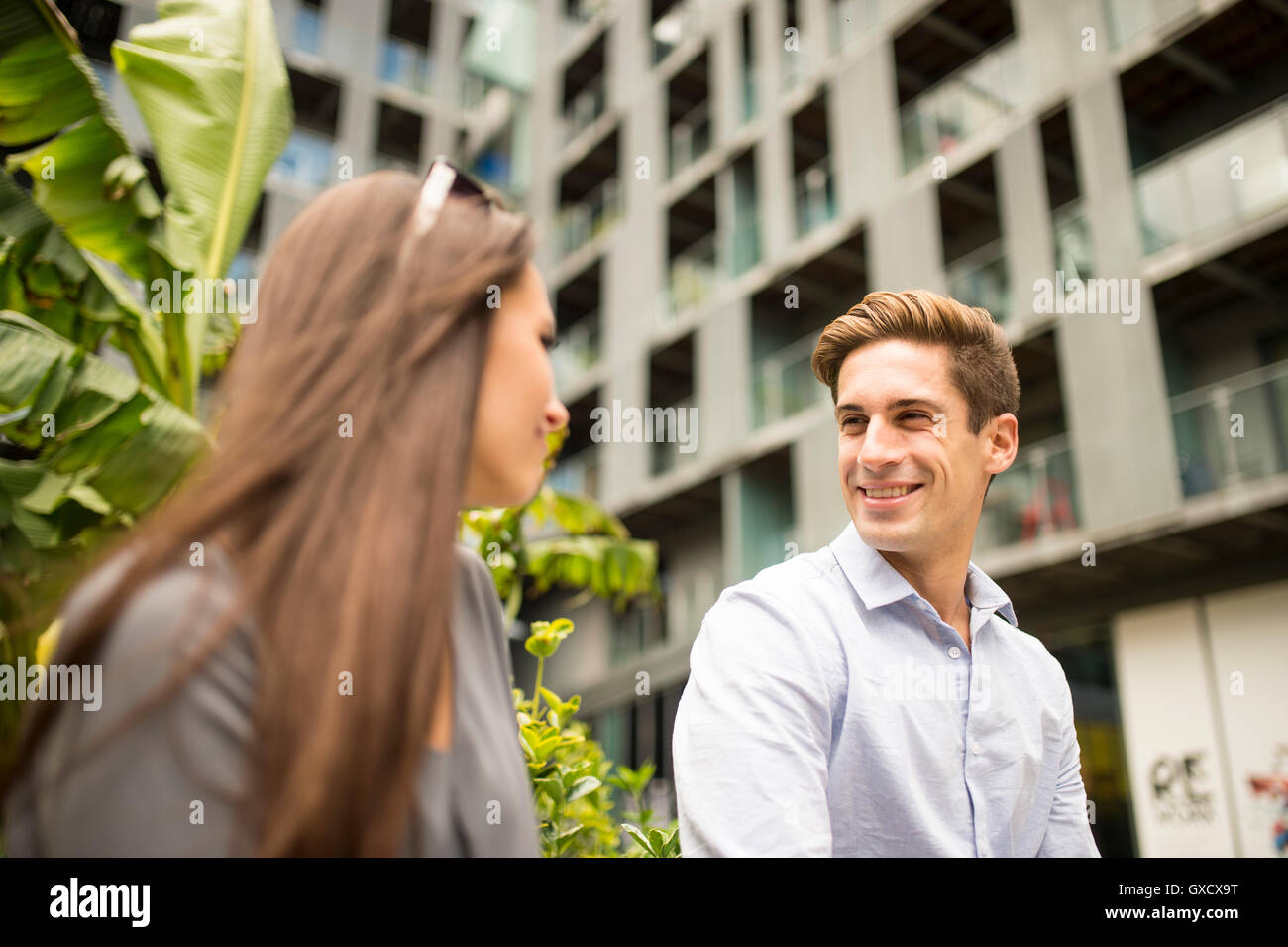 Young businesswoman and man chatting outside office, London, UK Stock Photo