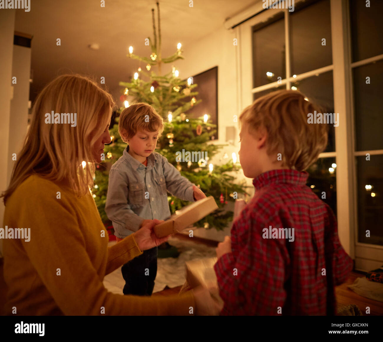 Mother and sons sitting at home at Christmas, exchanging gifts - Stock Image