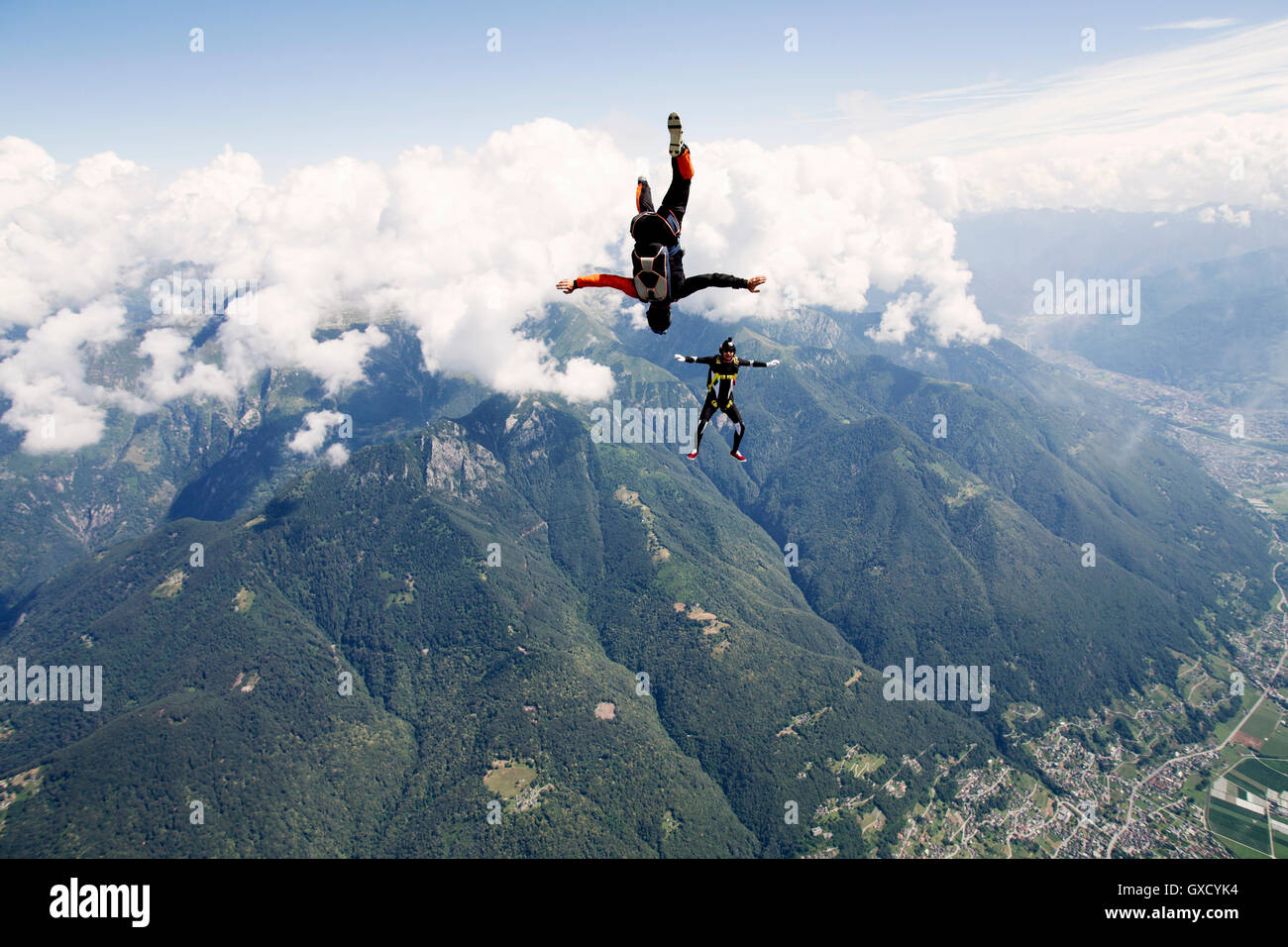 Freestyle skydiving team training, one man performing air-ballet, another filming with camera, Locarno, Tessin, - Stock Image