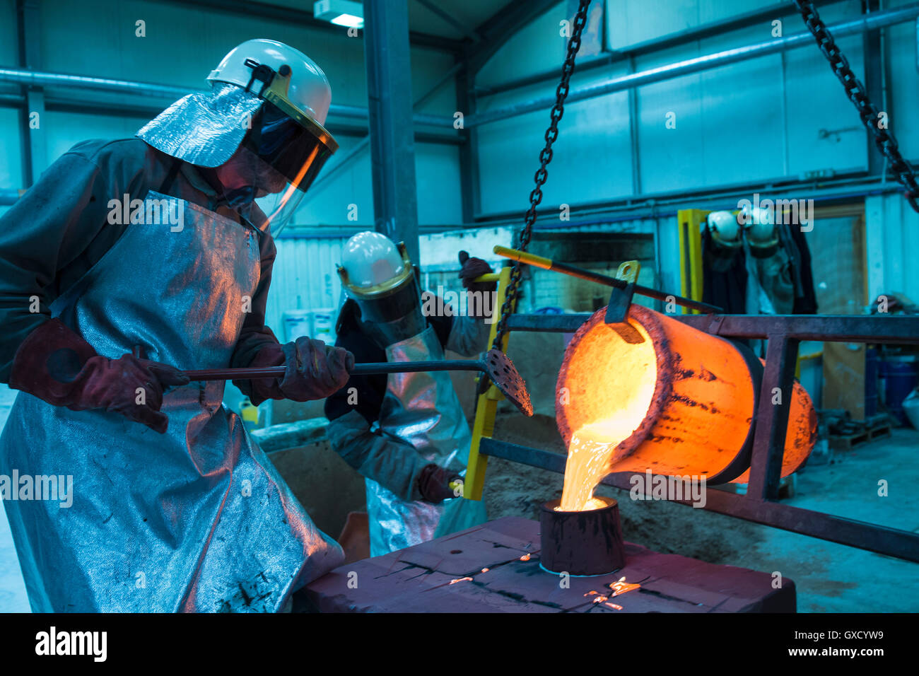 Male foundry workers pouring bronze melting pot in bronze foundry Stock Photo