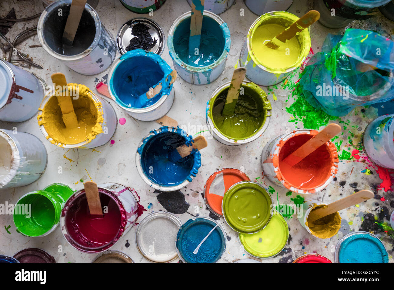 Overhead view of stirrers in paint pots in surfboard maker's workshop Stock Photo