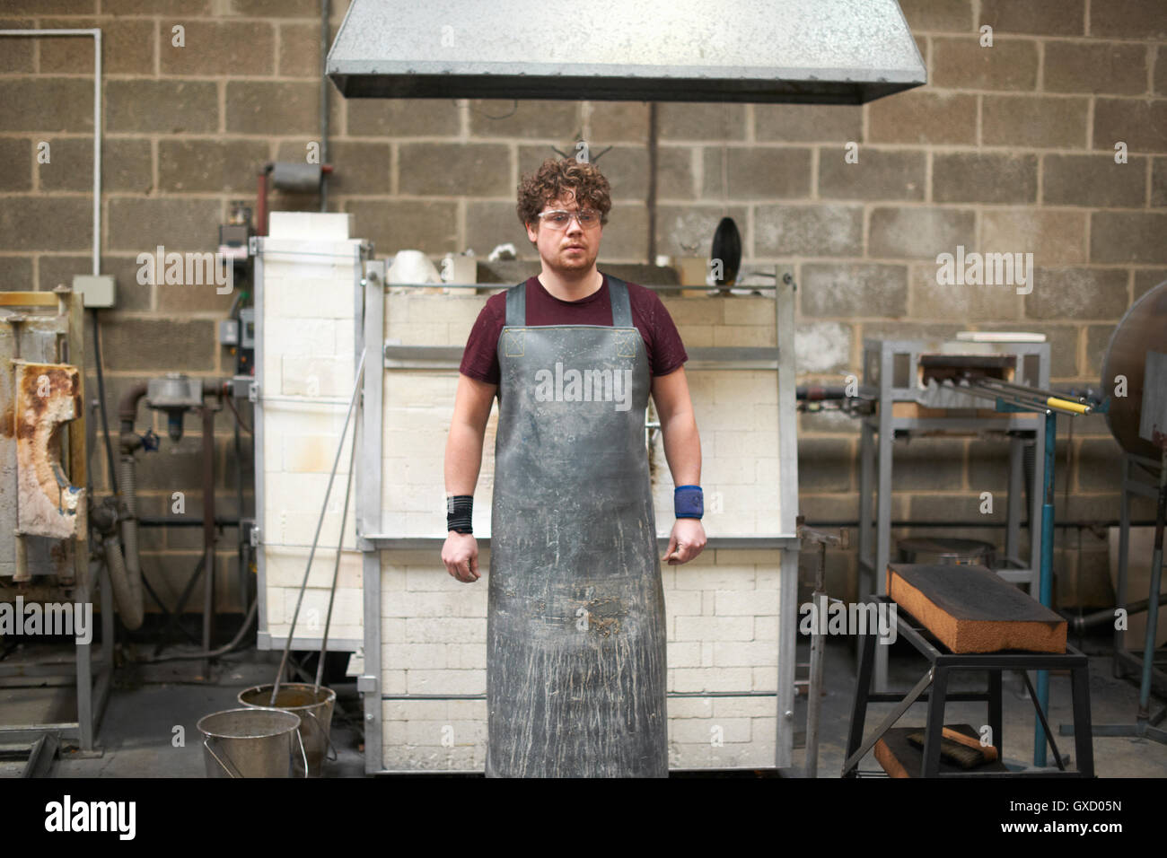 Portrait of glassblower in workshop wearing apron - Stock Image