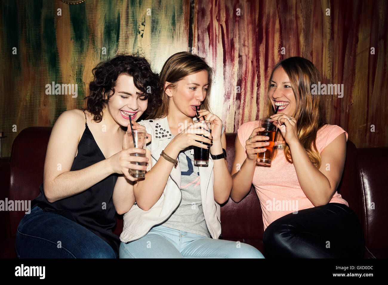 Three adult female friends drinking in bar - Stock Image