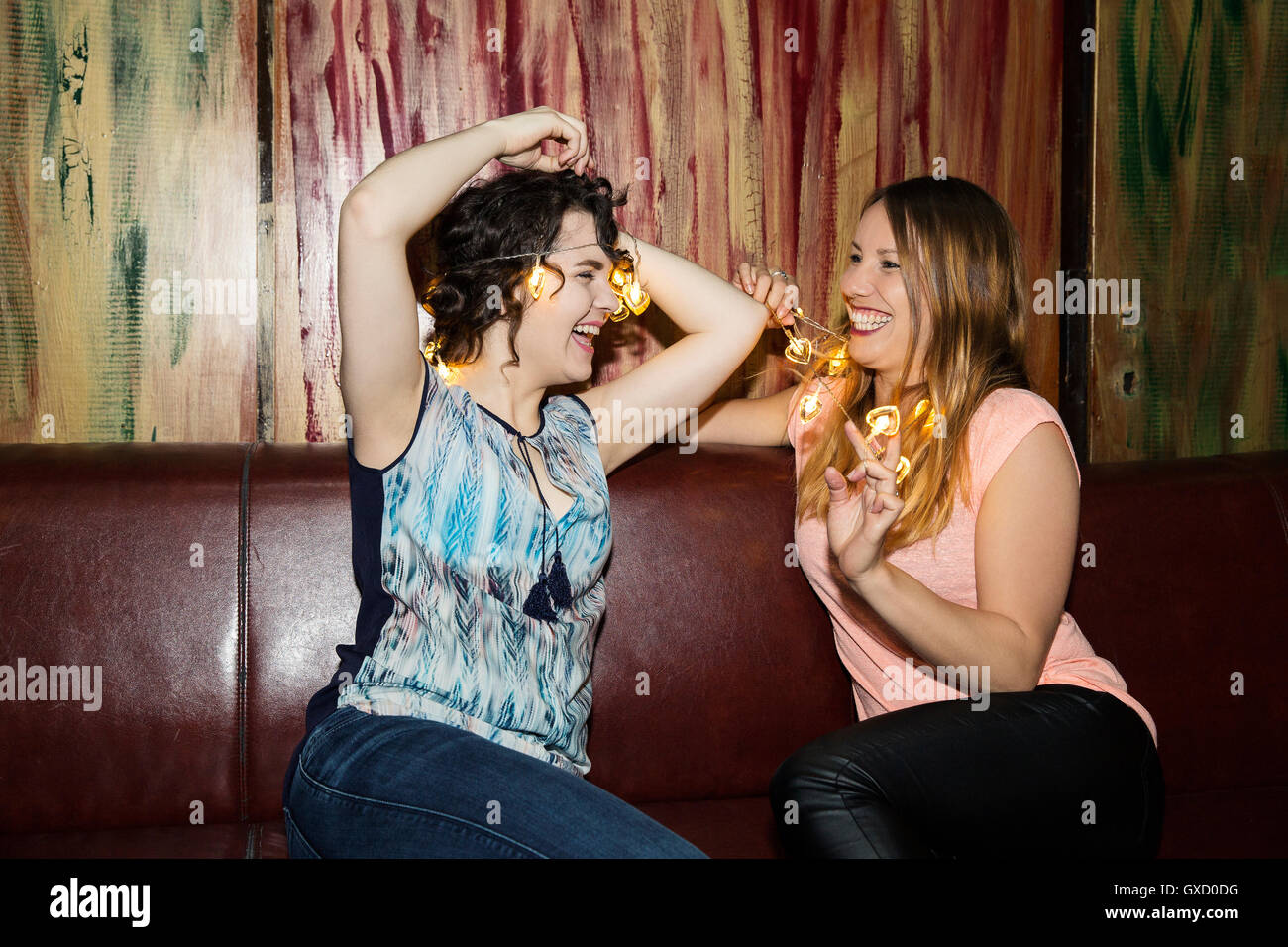 Two adult female friends putting on fairy lights on night out in bar - Stock Image
