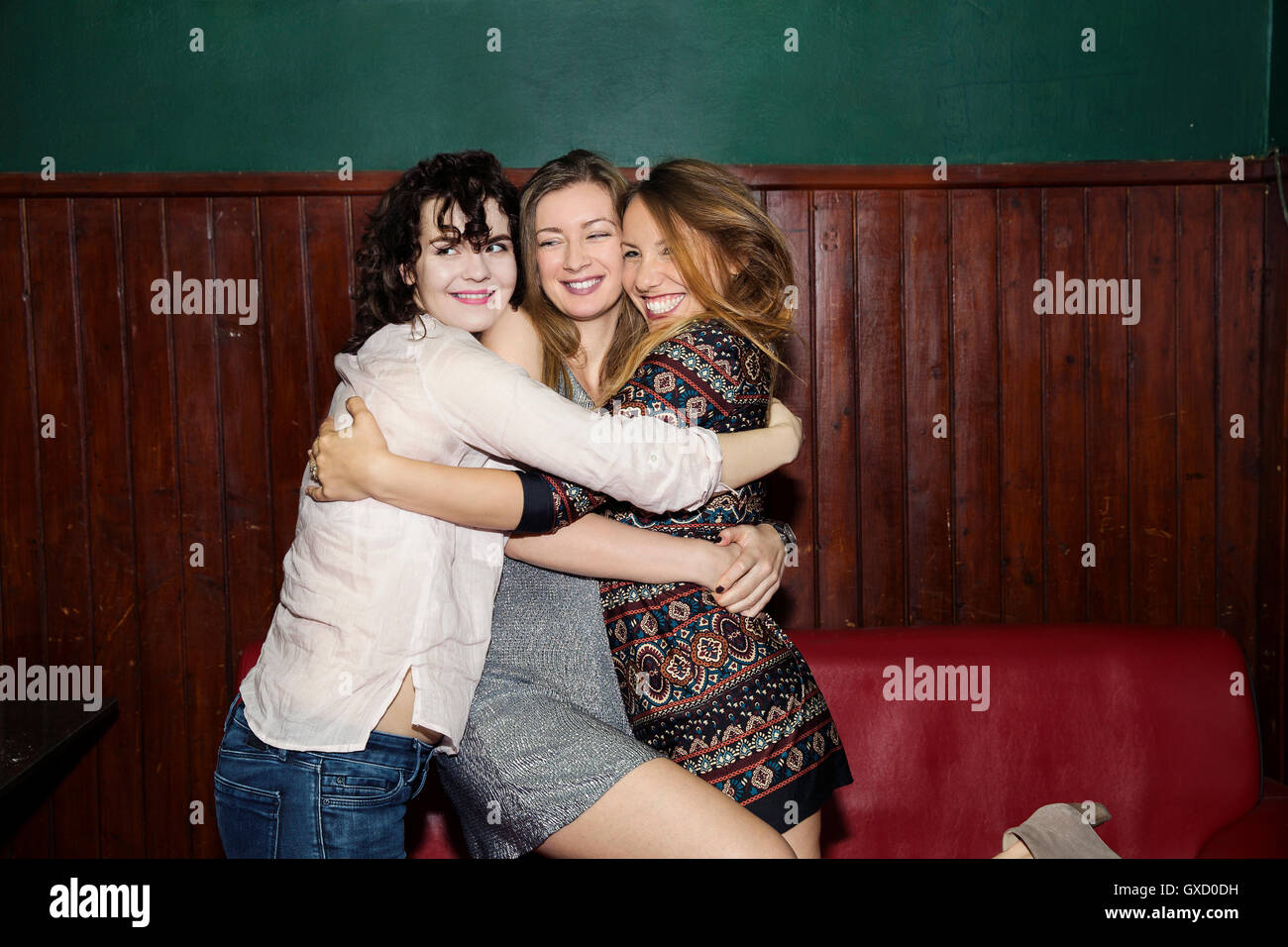 Three adult female friends having group hug in bar - Stock Image
