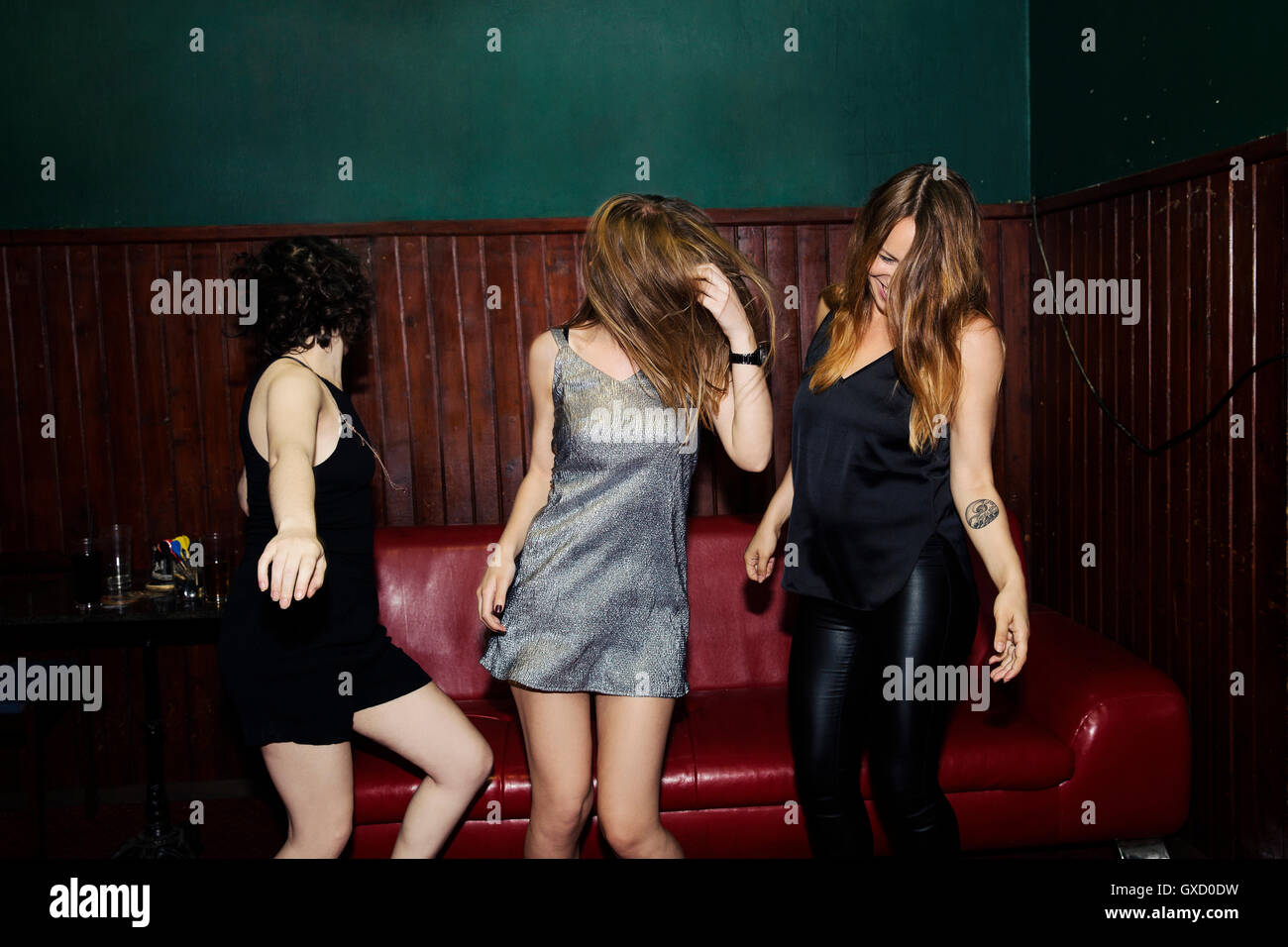 Three adult female friends dancing in club on night - Stock Image