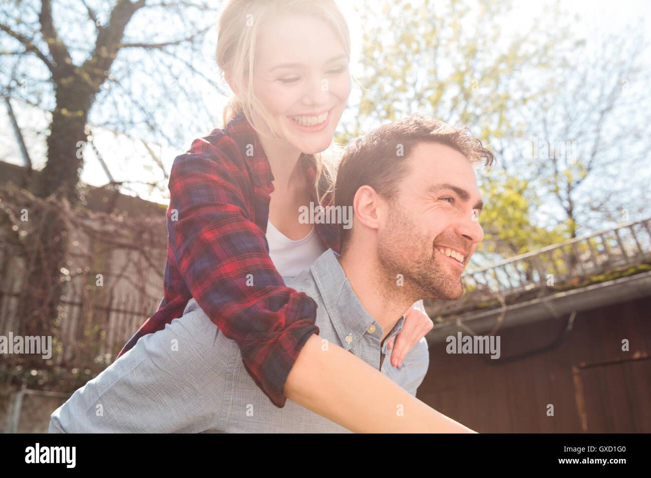 Man giving woman piggyback smiling - Stock Image