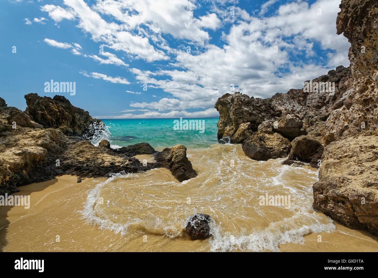 Hawaii beach and surf surrounded by volcanic rock taken on the big island of Hawaii with no people and surf pouring - Stock Image