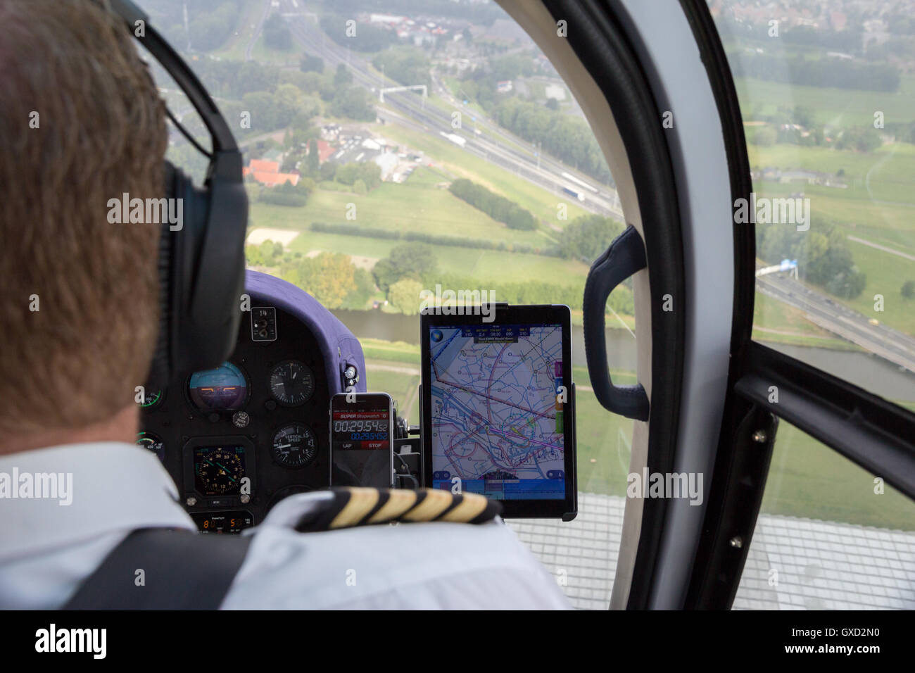 Helicopter pilot using tablet for chart navigation - Stock Image
