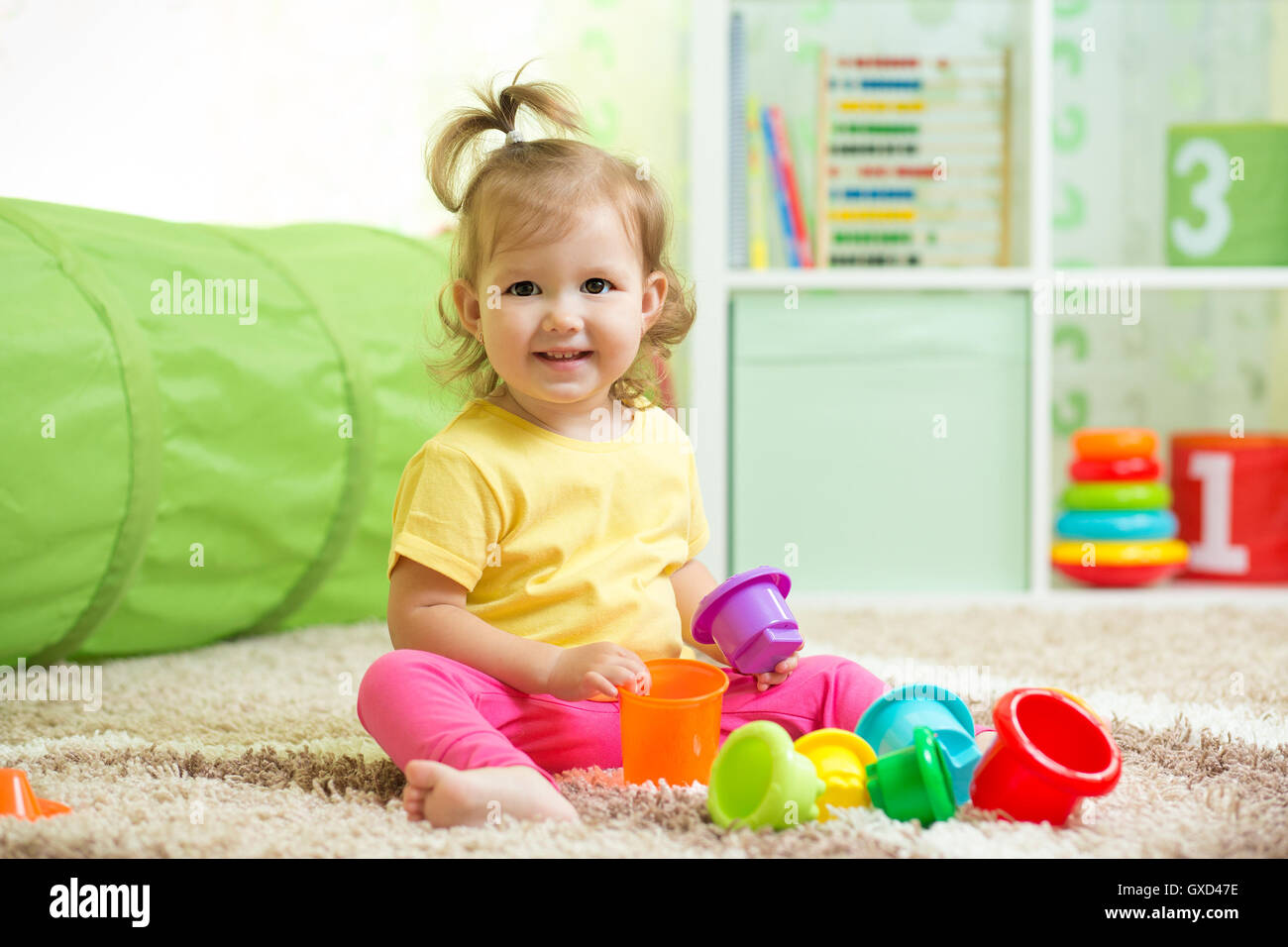 Cheerful kid toddler playing in nursery room - Stock Image