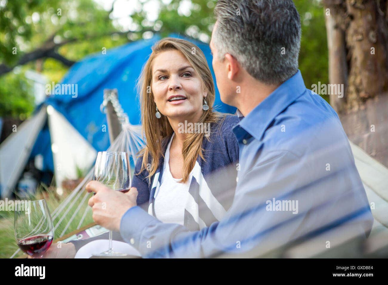 Mature couple chatting on hammock at garden party - Stock Image