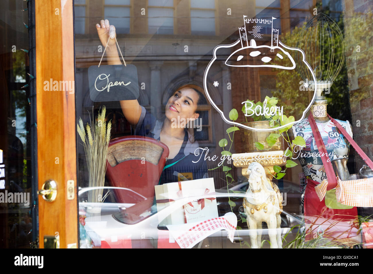 Female worker in bakery, turning sign to open - Stock Image