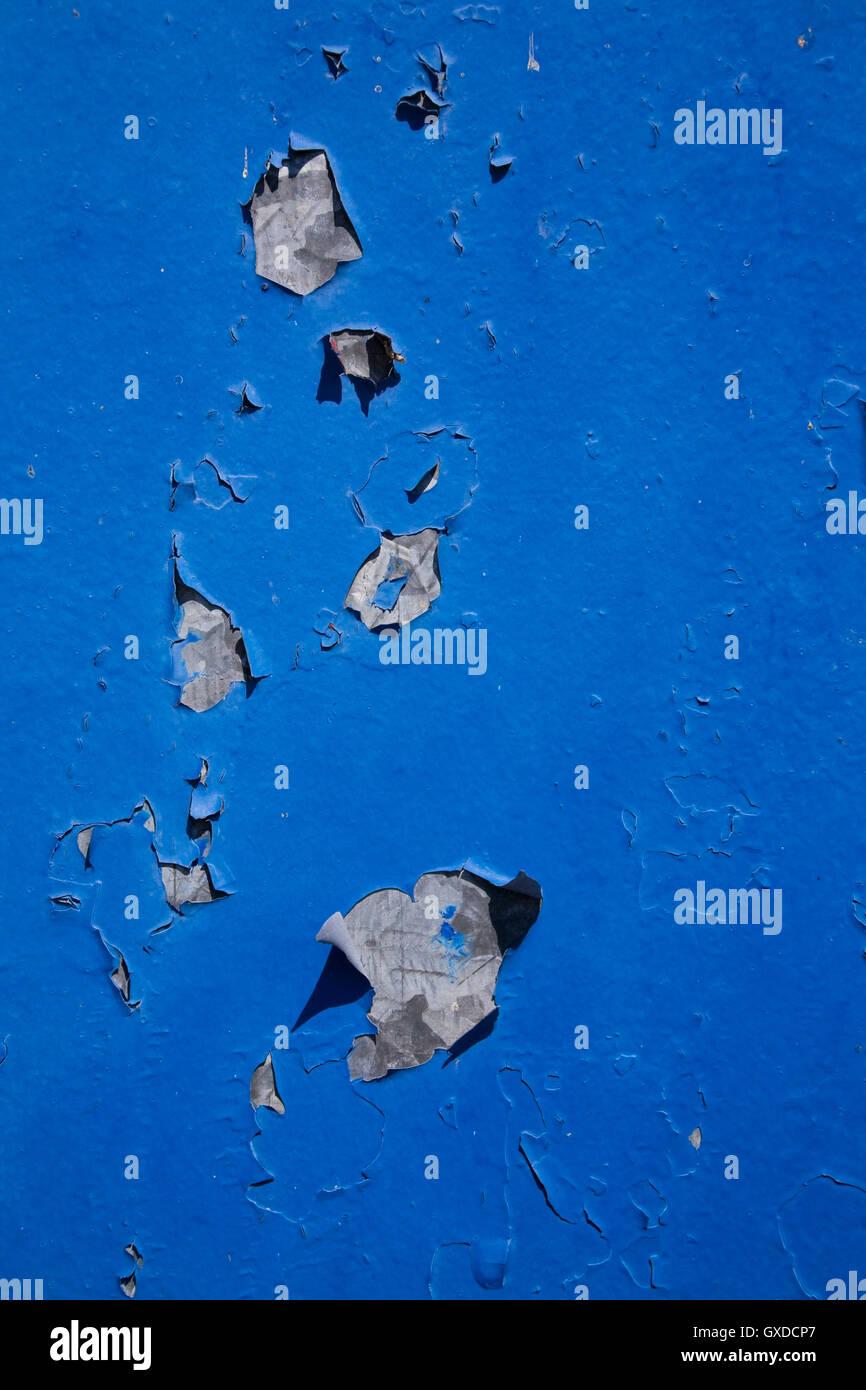 Peeling blue paint on metal surface - Stock Image