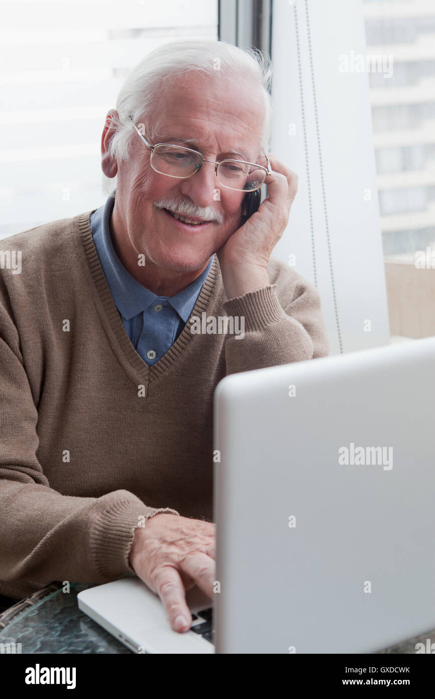 Senior man using mobile phone and laptop at home - Stock Image