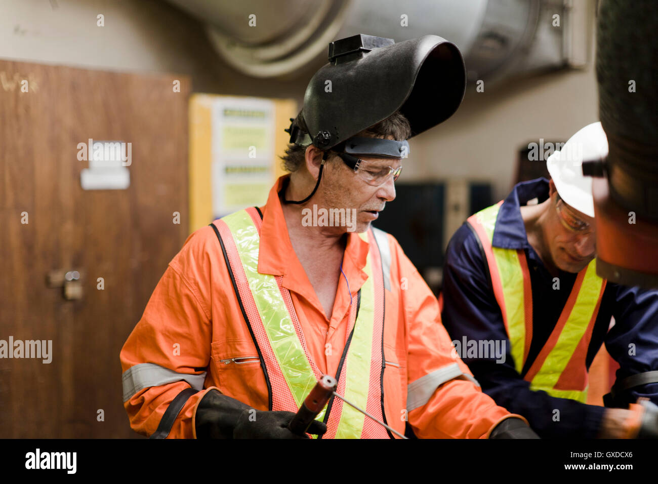 Welder and engineer in brainstorming session on oil rig - Stock Image