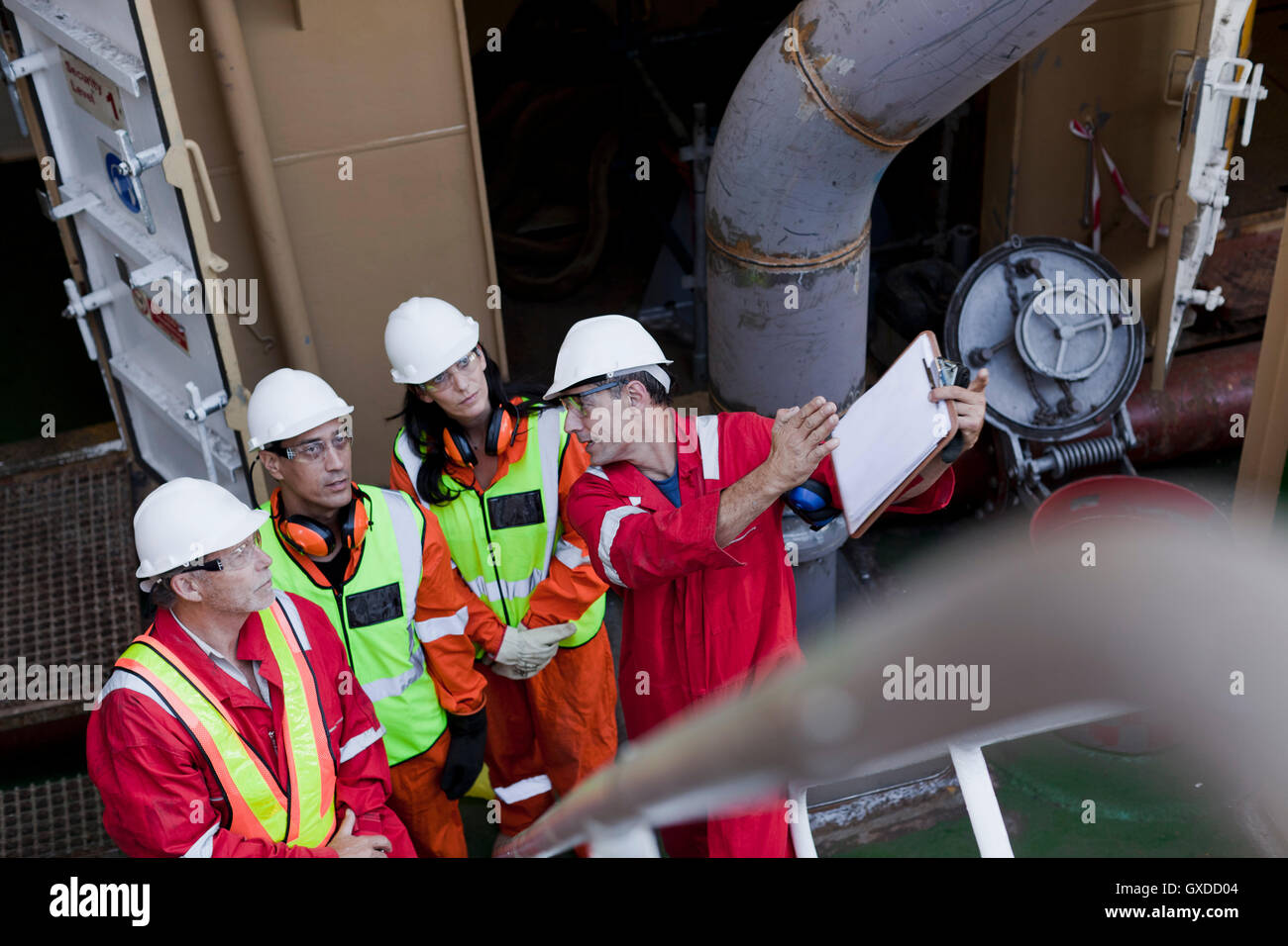 Engineers in brainstorming session on oil rig - Stock Image