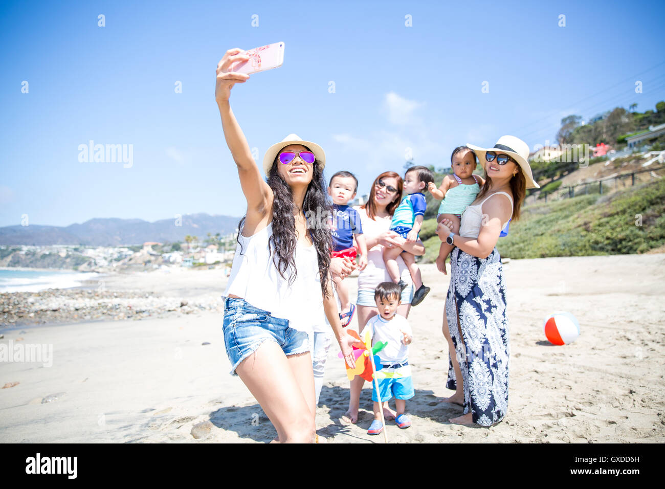 Mother taking selfie of friends and babies on beach, Malibu, California, USA - Stock Image