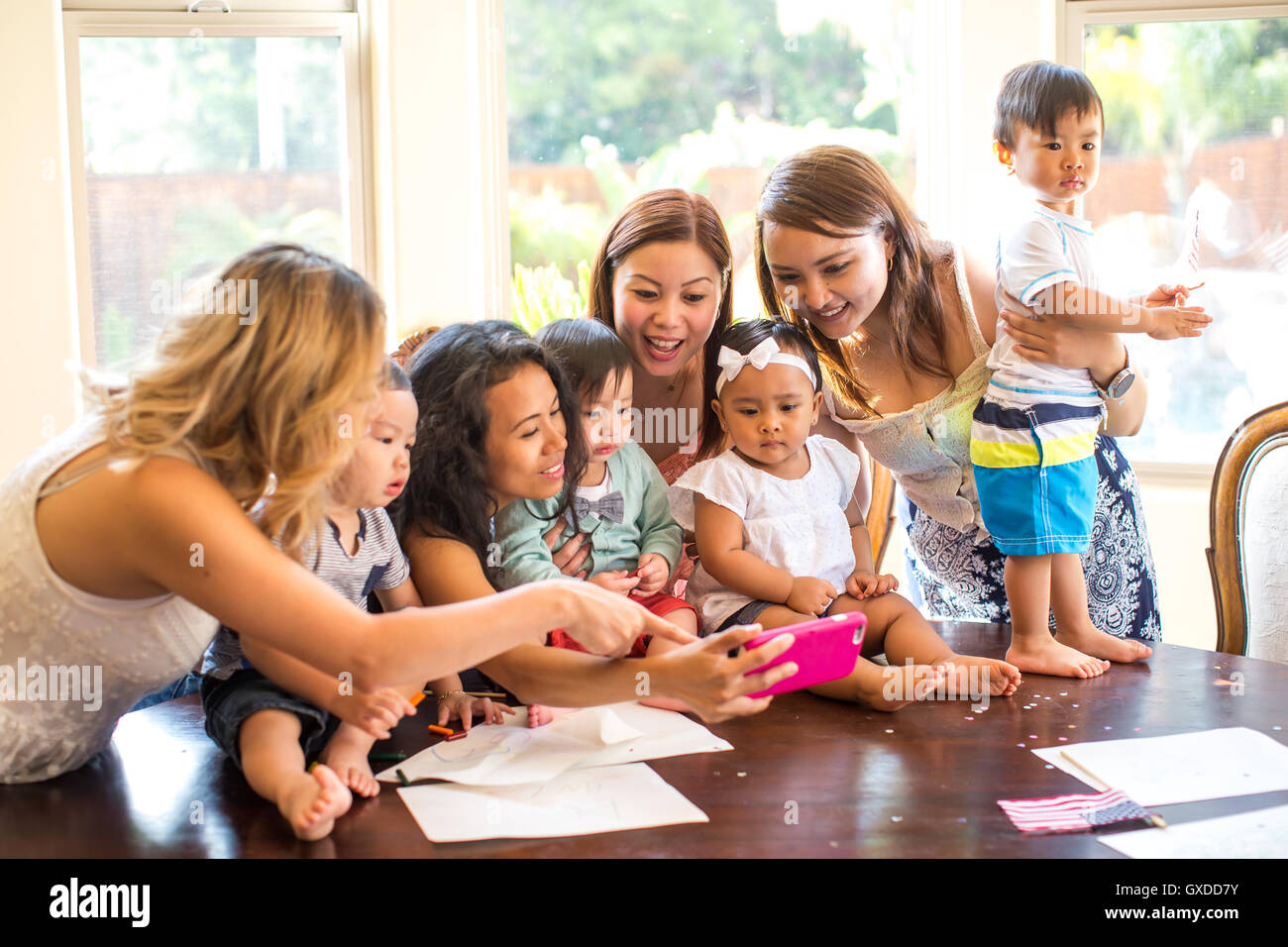 Woman taking selfie with mothers and babies at dining table - Stock Image