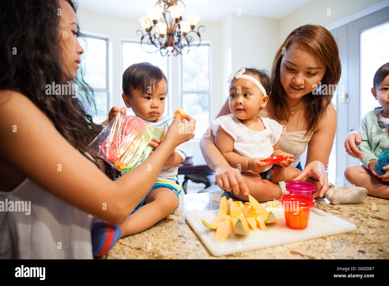 Women feeding baby son and daughter fruit on kitchen counter Stock Photo
