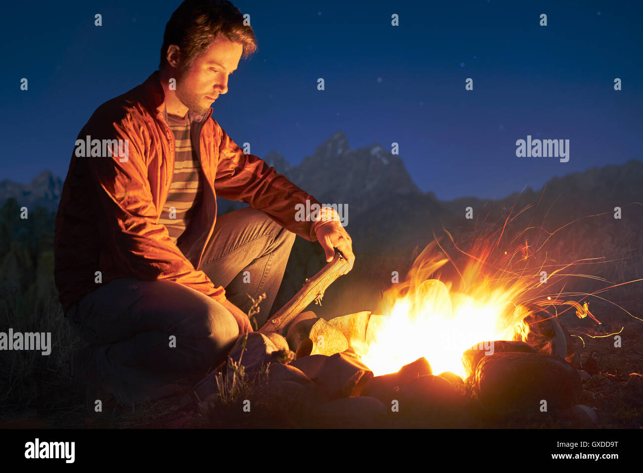Man crouching by campfire at night, Jackson, Wyoming, USA - Stock Image