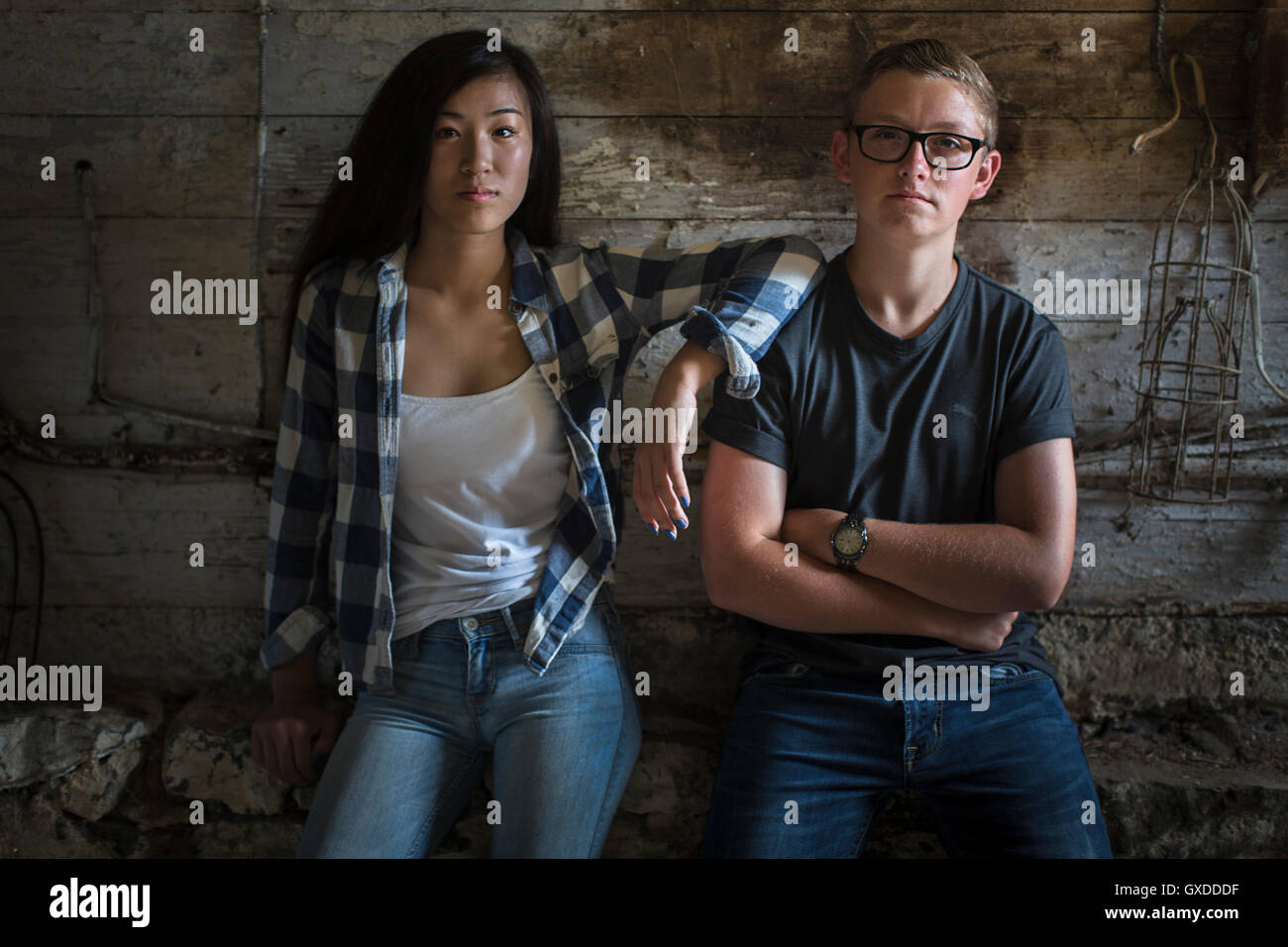 e1533099fe3 Portrait of sullen teenage couple leaning against dusty shed wall - Stock  Image