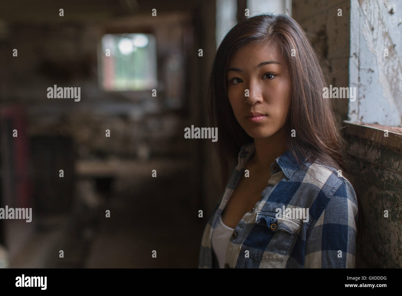 6b2c5de13d0 Portrait of sullen teenage girl leaning against dusty shed wall - Stock  Image