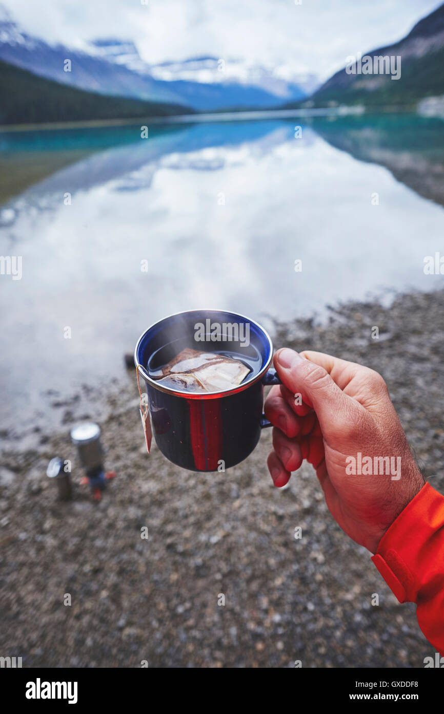 Cropped view of mans hand holding cup of tea by river, Banff, Alberta, Canada - Stock Image