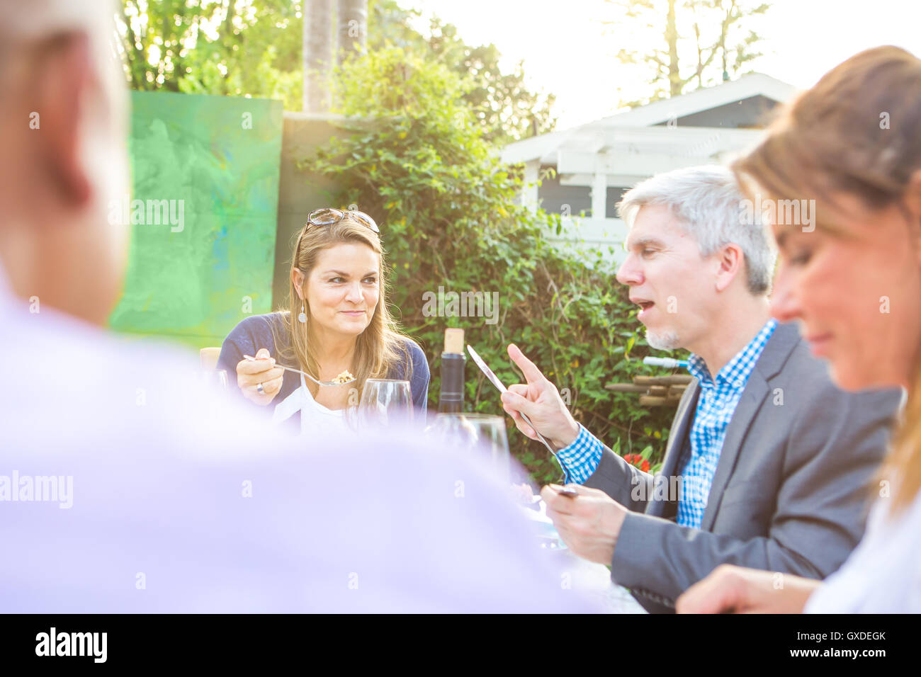 Mature adults eating and talking together at garden party table - Stock Image