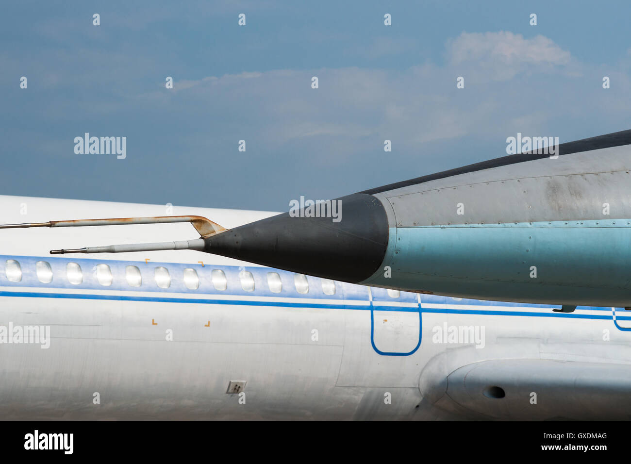Nose of a military aircraft against the background of a fuselage or body of a vintage civil passenger plane or airliner. - Stock Image