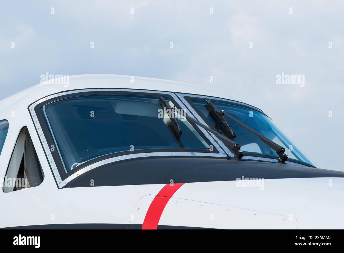 Stylish cockpit of a modern small aircraft. Windscreen and windshield wipers against the background of pale blue - Stock Image