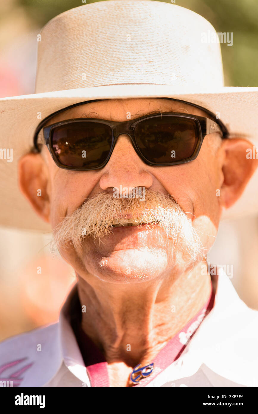 An elderly man in cowboy hat watches the Cheyenne Frontier