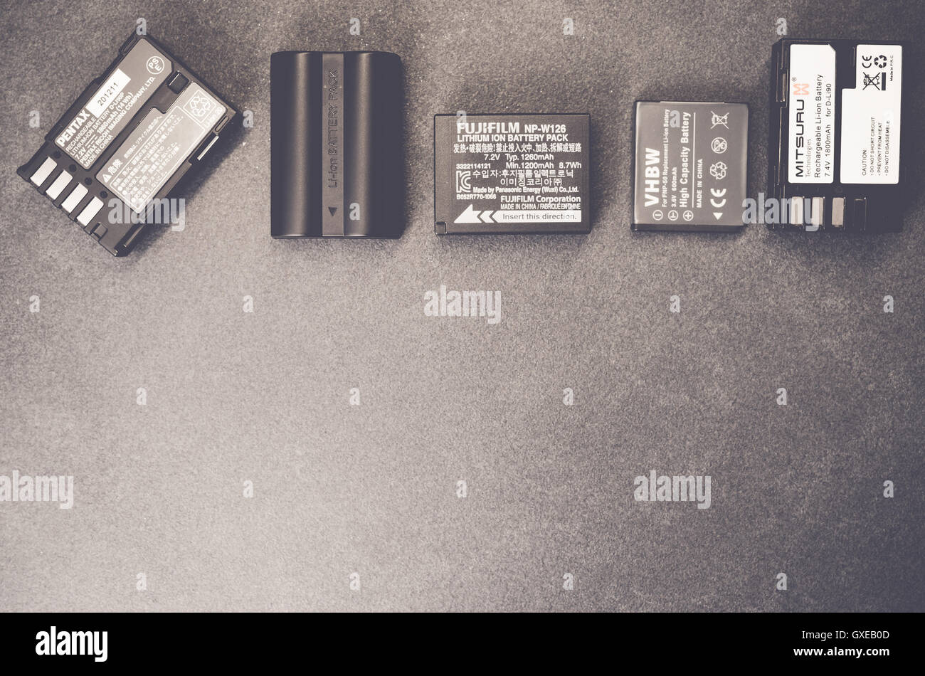 spare camera batteries on a slate worktop - Stock Image