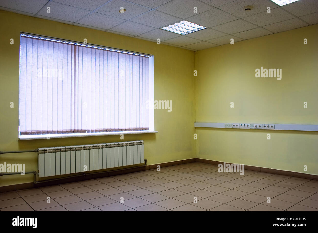 Corner of empty office room with floor of stones, ceiling, lamps ...