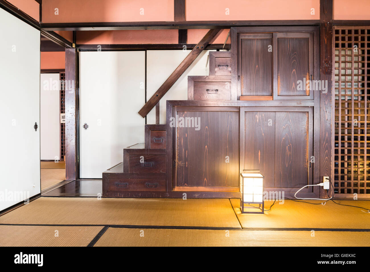 Japan, Izushi. Izushi Shiryokan museum, interior. Large tatami mat room with staircase with built in storage cupboard - Stock Image