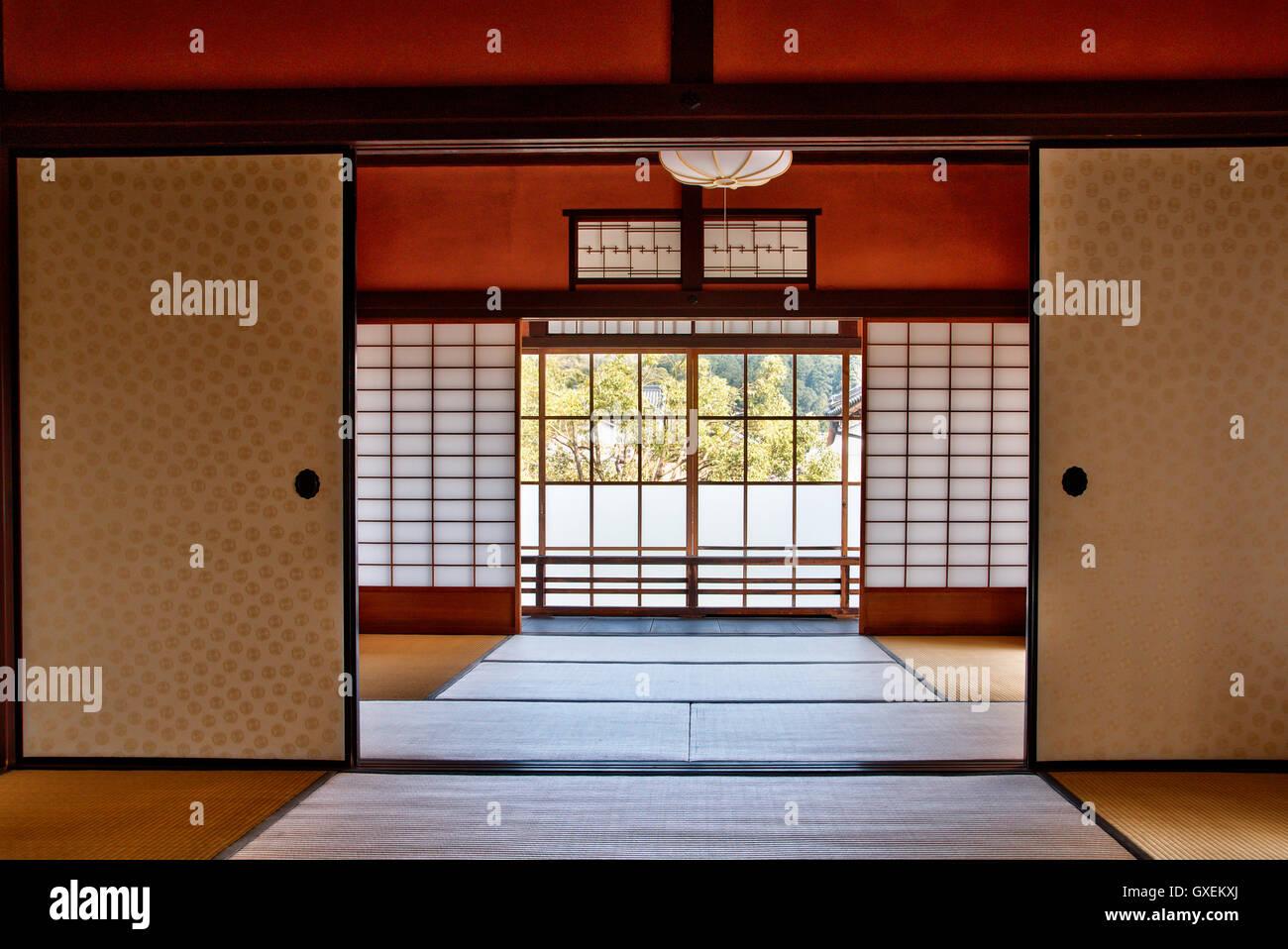 Japan, Izushi. Izushi Shiryokan museum, interior. Large Meiji period room opening onto another, then shuttered window - Stock Image