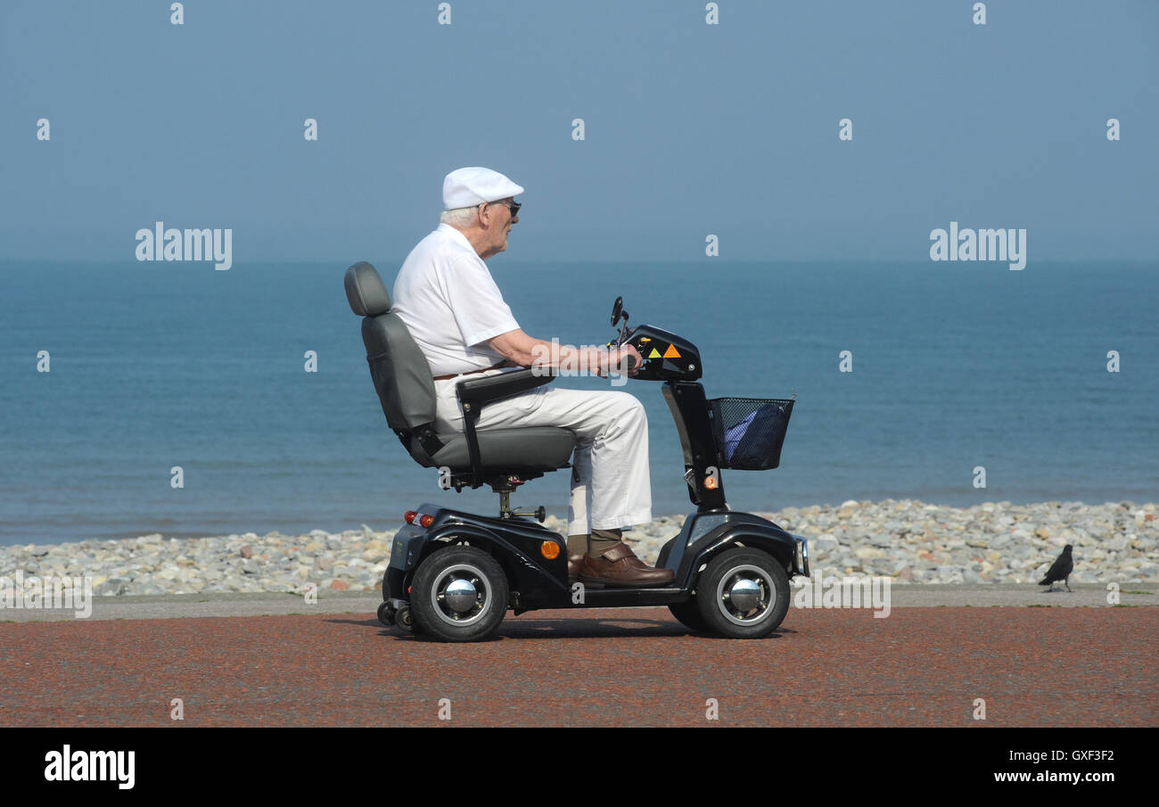 ELDERLY MAN RIDING DISABILITY SCOOTER ON COASTAL PROMENADE RE DISABLED HOLIDAYS SEASIDE PENSIONERS RETIREMENT PENSIONS - Stock Image