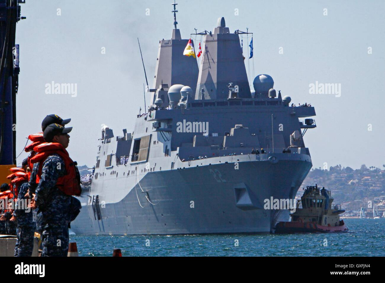 Line handlers stand by and prepare for USN San Antonio-class amphibious transport dock ship USS San Diego to approach - Stock Image