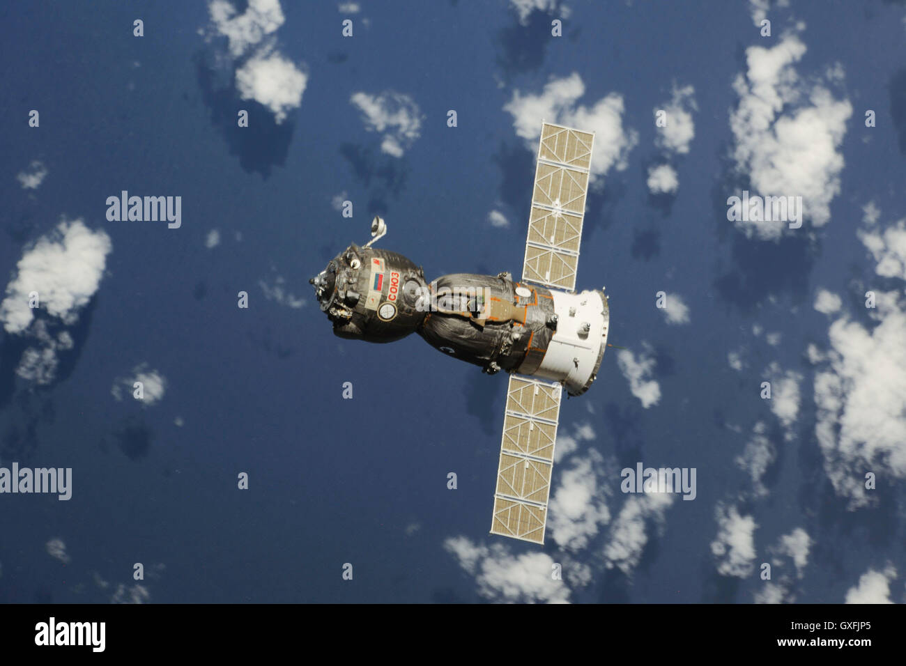 The Soyuz TMA-08M spacecraft travels towards the Earth's surface after undocking from the International Space - Stock Image