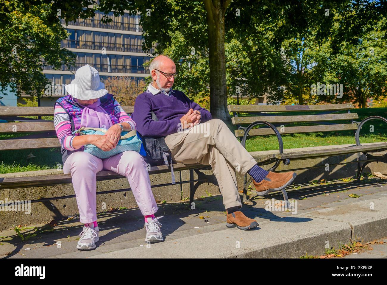 Elderly couple asleep on park bench - Stock Image