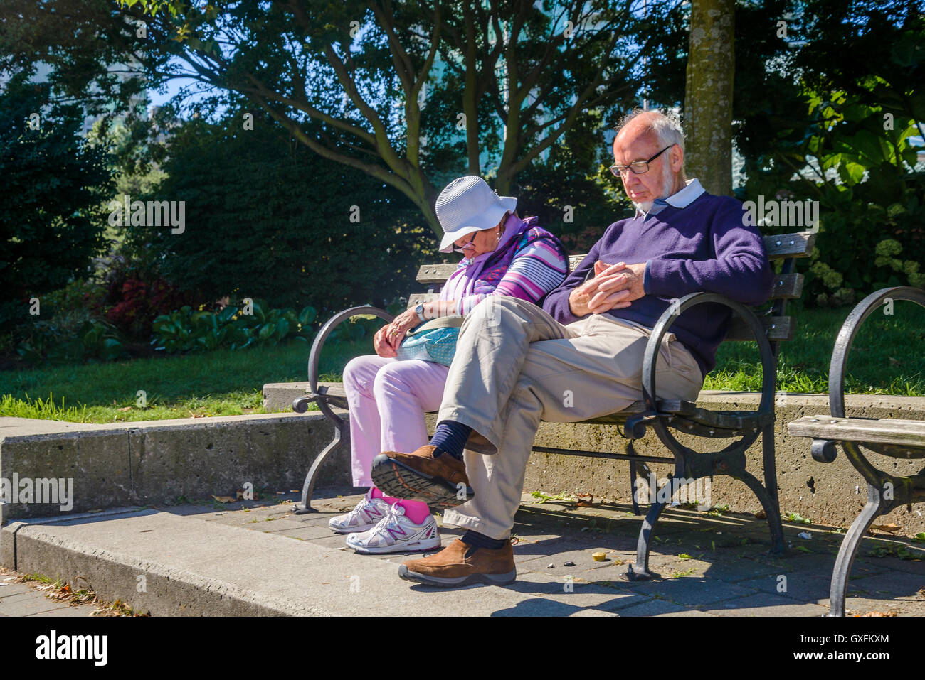Elderly couple asleep on park bench - Stock Image