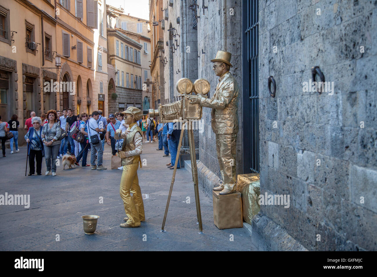 Street performers in Sienna, Italy. Street mimes acting like old time movie camera man and assitant. - Stock Image