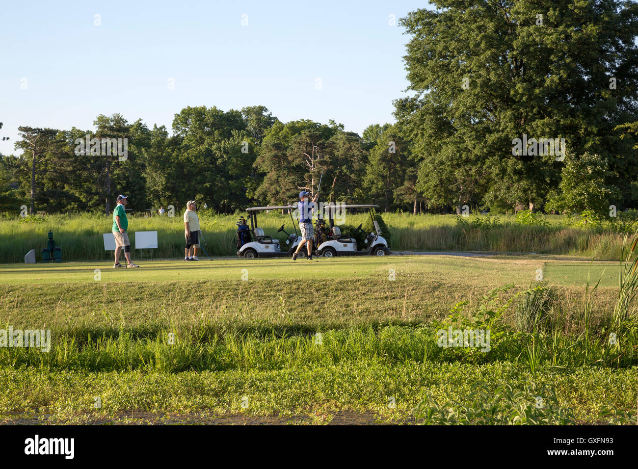 Men watching as another man tees off on golf course in park. late day blue sky. - Stock Image