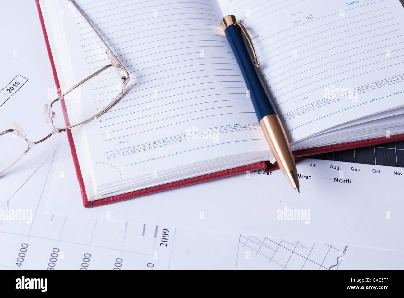 Notebook, pen and glasses on top of financial charts - Stock Image