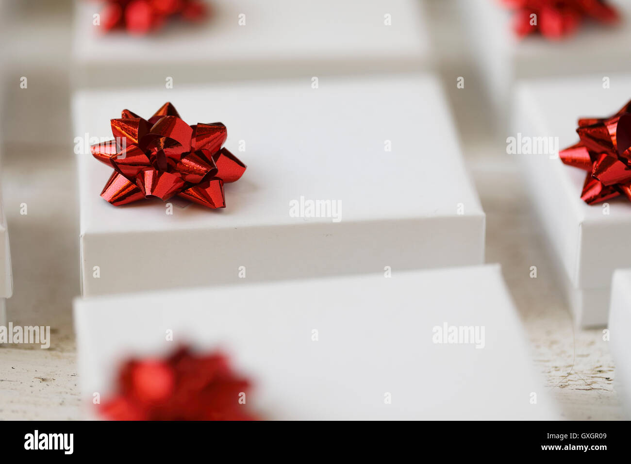 Close up of small white gift boxes with red bows. - Stock Image