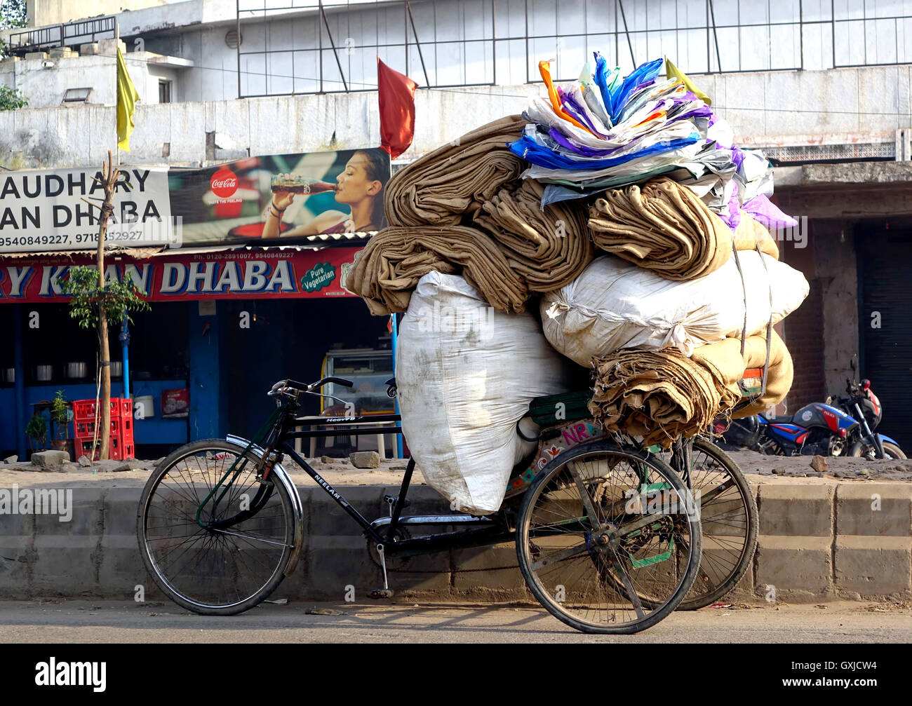 Indian street scene - load of sacs, bags and other miscellany on a man-pulled rickshaw. - Stock Image