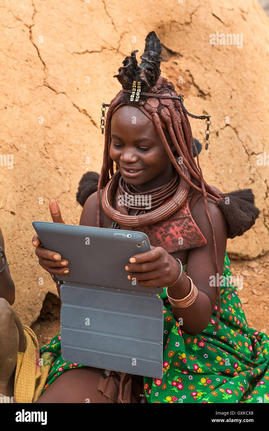 A Himba girl with an iPad, indigenous tribe, Kunene, Namibia - Stock Image