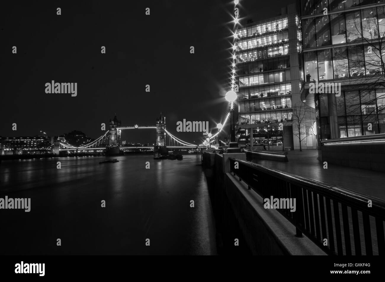 Tower Bridge lit up at night. Using a long exposure to smooth the water of the River Thames, March. Converted to - Stock Image